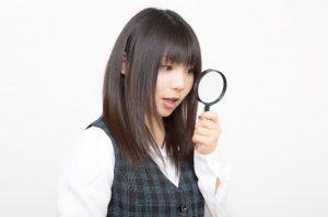 虫眼鏡をみる女性